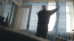 Senior opens the curtains in the room and the light gets in the room. Old - stock footage