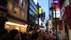 View of Myeongdong street with neon store signs agaginst Seoul tower in Seoul - stock footage
