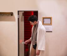 Young man in bathrobe entering or exiting sauna Stock Photos