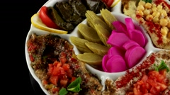 Plate of assorted Arabic appetizer with pickled cucumbers and turnips, loop - stock footage