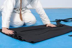 An aikidoka girl folding her hakama for Aikido training - stock photo