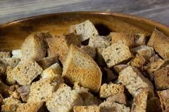 Homemade croutons on wooden background Stock Photos