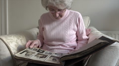 Senior woman looks at old photographs in album - stock footage