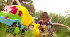 Boy playing and digging with toy excavator in garden Stock Footage