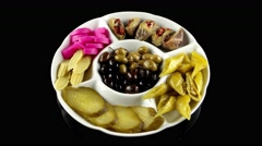 Plate of Arabic pickles (eggplant, cucumbers, turnips, olives), loop, top view - stock footage