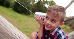 Cute little Boy curiously listening on tin can phone in park Stock Footage