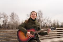 Smiling woman with a guitar - stock photo