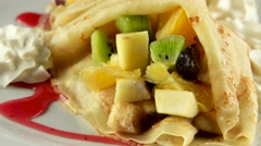 Tasty pancakes with tropical fruits and whipped cream, loop Stock Footage