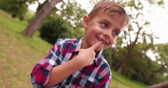 Cute little Boy in park smiling and looking at camera Stock Footage