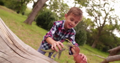 Little boy playing with dinosaur toys in garden Stock Footage