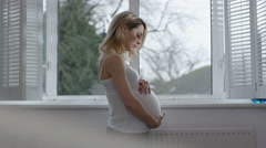 4K Portrait of pregnant woman at home, feeling her tummy & looking out of window - stock footage