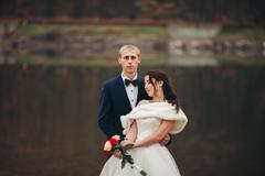 Love and passion - kiss of married young wedding couple near lake - stock photo