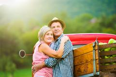 Senior couple hugging, vintage styled red car, sunny nature - stock photo
