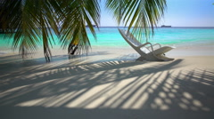 Forgotten beach chair on a tropical beach in the ocean waves. - stock footage