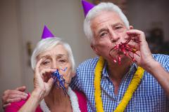 Portrait of senior couple blowing party horn - stock photo