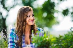 Gardener in blue checked shirt in her sunny garden - stock photo