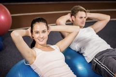 Man and woman doing abdominal crunches on fitness ball Stock Photos