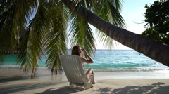 Young slim woman enjoying vacation on a sun lounger on a tropical beach. - stock footage
