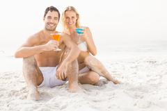 Happy couple sitting and drinking cocktails - stock photo