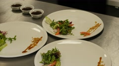 Dressing up a delicious salad in a restaurant kitchen, close up - stock footage