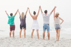 Cute group of friends holding hands and outstretching their arms on the beach Stock Photos