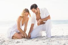 Couple having fun on the beach on a sunny day Stock Photos
