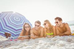 Happy friends lying and taking a selfie on the beach Stock Photos