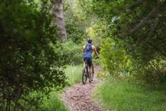 Rear view of man riding bicycle  on dirt road amidst trees in forest Stock Photos