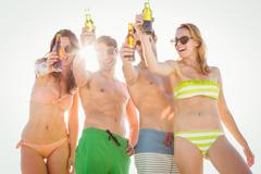 Happy friends drinking beer and toasting on the beach Stock Photos