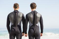 Handsome men facing the ocean in wetsuits on the beach Stock Photos