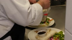 Preparing tasty tex mex tortilla wraps in a restaurant kitchen filled with salad Stock Footage