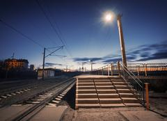 Stock Photo of Rural railway station at night with blue sky. Railroad