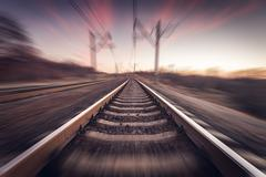 Stock Photo of Railway station at colorful sunset with motion blur effect. Railroad