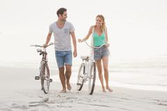 Cute couple walking next to their bicycles on the beach Stock Photos