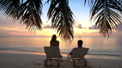 Couple on a tropical beach are admiring the sunset. Stock Footage
