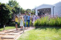 Multi-generation family walking together on the garden path Stock Photos