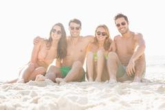 Happy friends sitting on the beach on a sunny day Stock Photos