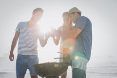 Cute group of friends having a barbecue and beers on the beach Stock Photos
