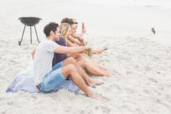 Group of friends sitting on the sand taking selfie with selfie stick Stock Photos