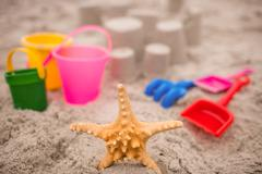 Sandcastle with bucket and spade at beach on a sunny day Stock Photos