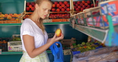 Young woman choosing pears in fruit shop Stock Footage