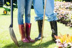 Lower section couple in wellington boots and shovel standing in their garden Stock Photos