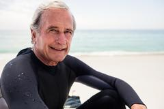 Portrait of happy senior man in wetsuit sitting on beach on a sunny day Stock Photos