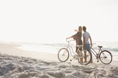 Cute couple walking next to bicycles on the beach Stock Photos