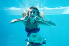Woman doing thumbs up underwater in swimming pool Stock Photos