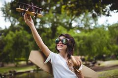 Girl playing with a toy aeroplane at park Stock Photos
