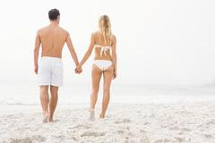Happy couple posing on the beach on a sunny day Stock Photos