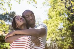 Young couple cuddling in the park on a sunny day Stock Photos