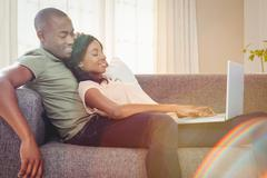 Young couple using a laptop while relaxing on a sofa in the living room Stock Photos