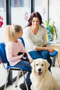 Happy mother and daughter with dog in vet waiting room Kuvituskuvat